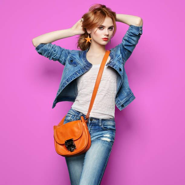 mode porträt von schöne junge frau mit handtasche - handtasche jeans stock-fotos und bilder