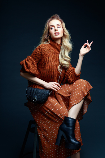 Portrait of long hair blond young woman wearing brown sweater and skirt, holding black purse, sitting on chair, looking away. Studio shot against black background.