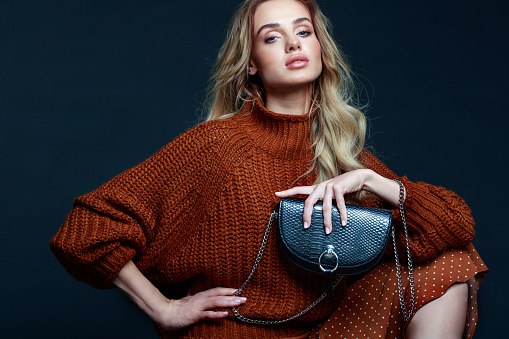 Portrait of long hair blond young woman wearing brown sweater and skirt, holding black purse, looking at camera. Studio shot against black background.