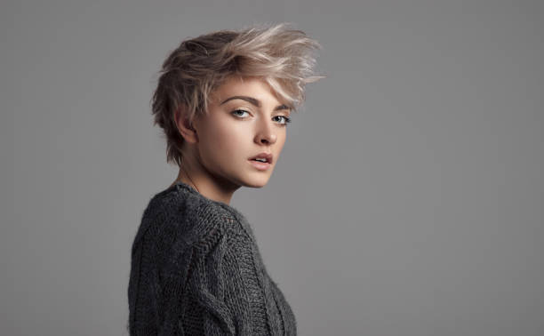 Fashion portrait of female model with blond short hair wear sweater Fashion portrait of female model with blond short hair wear sweater short hair stock pictures, royalty-free photos & images