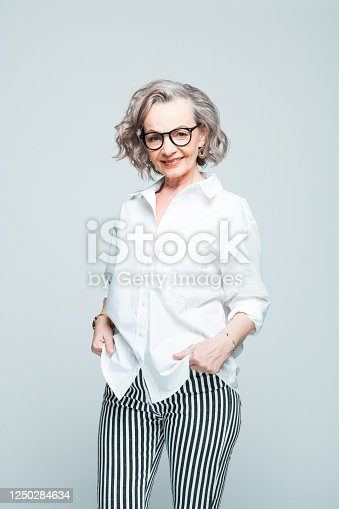 Elderly lady wearing white shirt, striped trousers and glasses standing against grey background, smiling at camera. Studio shot of female designer.