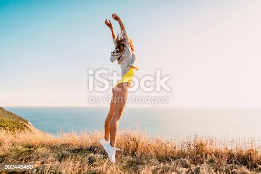 istock Fashion portrait of jumping happy woman in nature. Sporty woman outdoor 902448480