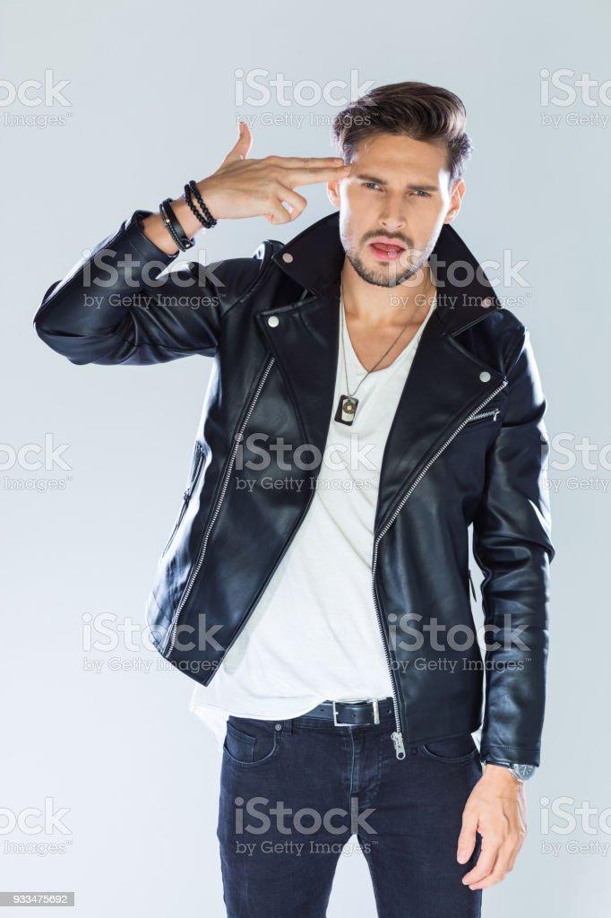 Fashion portrait of macho wearing leather jacket Fashion portrait of handsome man wearing black leather jacket. Studio shot, grey background. 25-29 Years Stock Photo