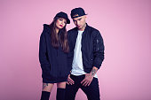 Studio portrait of young couple wearing black clothes and baseball caps, standing against pink background.