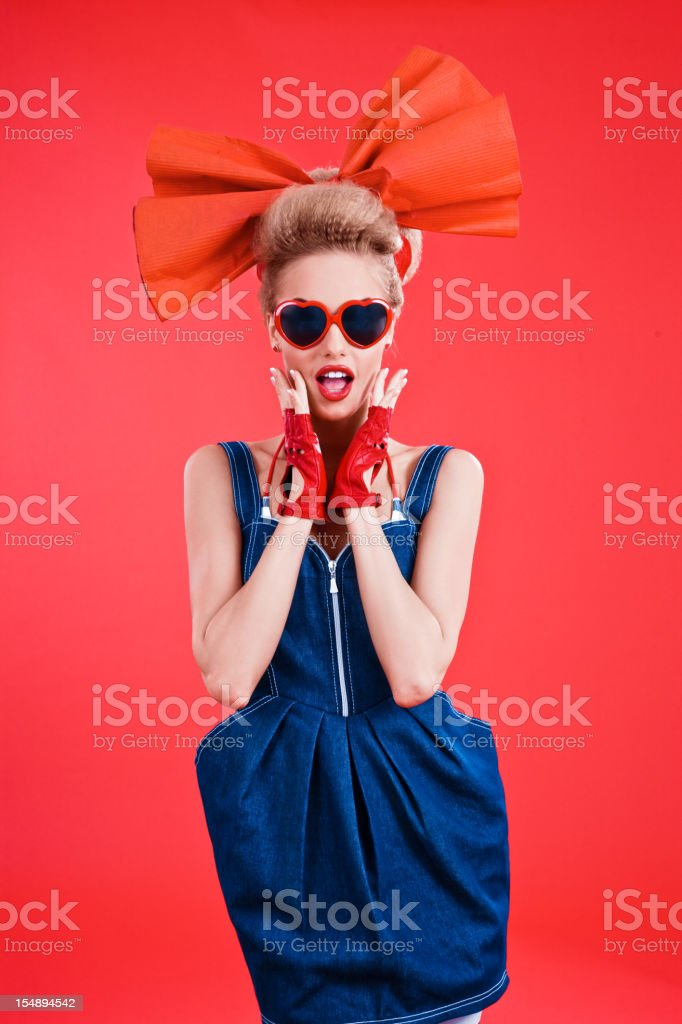 Fashion portrait of woman posing against red background stock photo