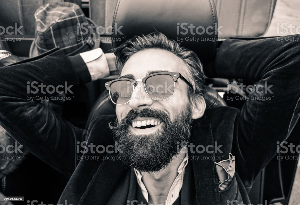 Fashion portrait of young bearded man ready for road trip - Cheerful hipster guy sitting in car looking the sky - Black and white editing - Soft focus on beard - Warm vintage retro filter stock photo