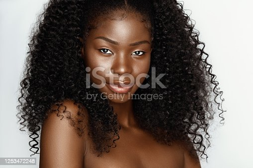 istock Fashion portrait of young beautiful african american woman with curly hair againstgray background 1253472248