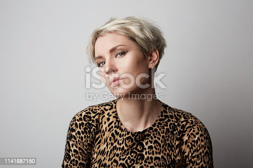 Fashion Portrait of young beautiful trendy girl with leopard dress looking at camera over white empty background