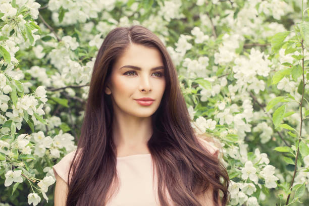 fashion portrait of young brunette woman with long brown hair and makeup on blossom spring flowers background - spring fashion stock pictures, royalty-free photos & images