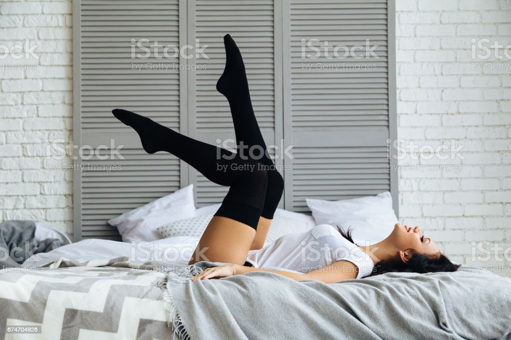 Fashion portrait of young happy elegant sexy woman in bed stock photo
