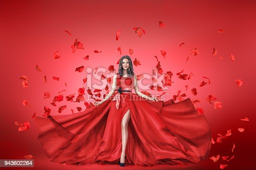 Fashion portrait of young woman in long red dress with flying petals