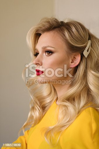 Side view closeup portrait of woman with creative elegant blondes hairstyle. Medium length wave blonde hair. Perfect red matte lips. Hollywood makeup. Stylish look. Beauty service concept.