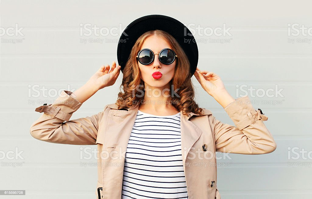 Fashion portrait pretty sweet woman blowing red lips, black hat Fashion portrait pretty sweet young woman blowing red lips wearing a black hat sunglasses coat over grey background Fashion Stock Photo