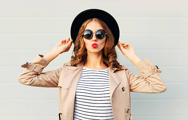 fashion portrait pretty sweet woman blowing red lips, black hat - fashion стоковые фото и изображения
