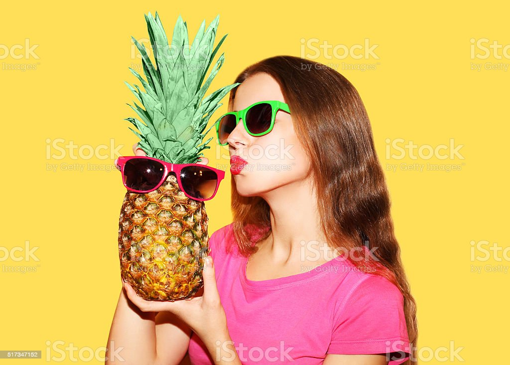 Fashion portrait pretty woman and pineapple in sunglasses over yellow stock photo
