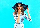 ... Mode portrait jolie femme en paille été chapeau est envoie un baiser  aérien sur fond bleu  Bouchent portrait de glamour jeune jolie fille ... bbcfe9759991