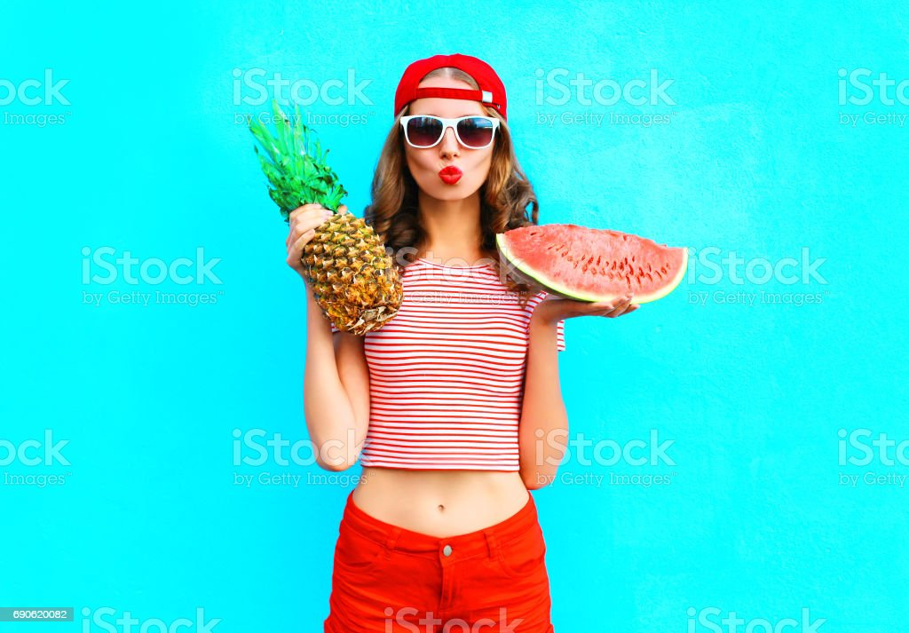 5c8ee4e72dd Fashion portrait pretty woman is holding a pineapple and a slice of  watermelon over a colorful blue background wearing a red baseball cap -  Stock image .