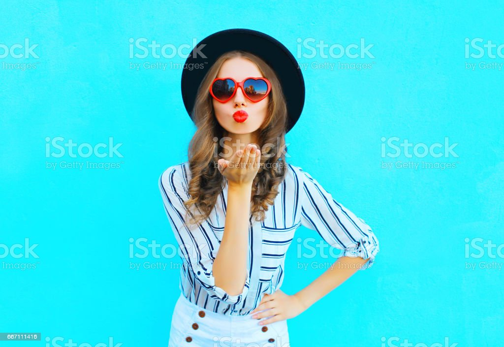 Fashion portrait pretty woman with red lips is sends an air kiss in a sunglasses shape of heart over  blue background stock photo