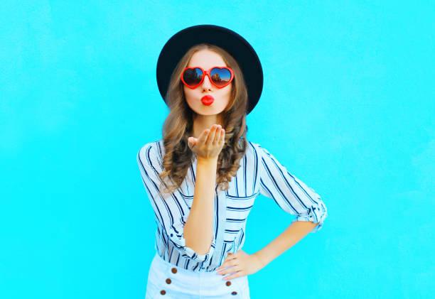 Mode portrait jolie femme avec des lèvres rouges est envoie un baiser de  l air 8c222aa0eade