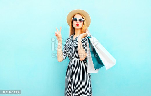 istock Fashion portrait pretty woman with shopping bags in striped dress, summer round straw hat on blue background 1029731932