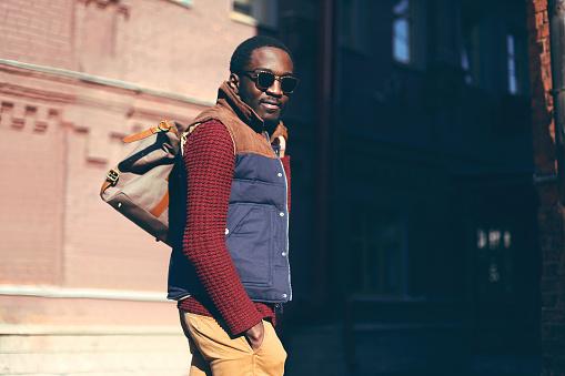 627398448 istock photo Fashion portrait stylish african man wearing bag in evening city 636345394