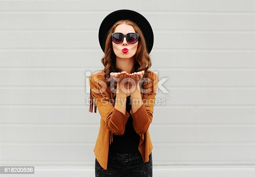 529664088istockphoto Fashion portrait woman blowing red lips sends air sweet kiss 618200536