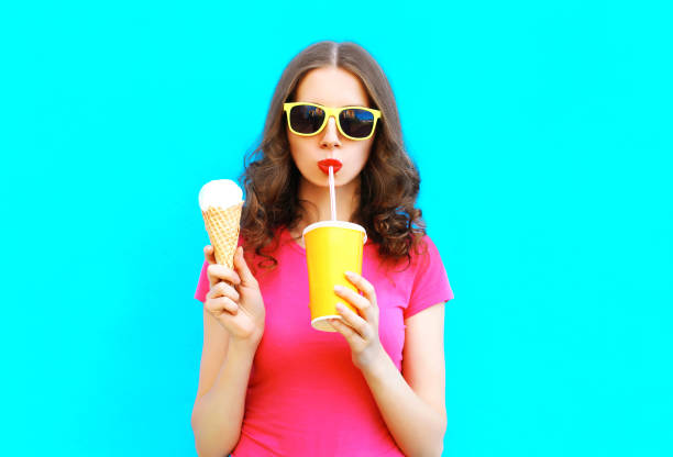 Fashion portrait woman drinks fruit juice from cup and holds ice cream over colorful blue background stock photo