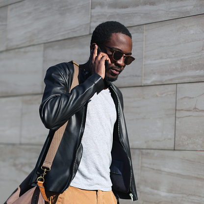 627398448 istock photo Fashion portrait young confident african man walking and talking on the smartphone in a evening city 809354000