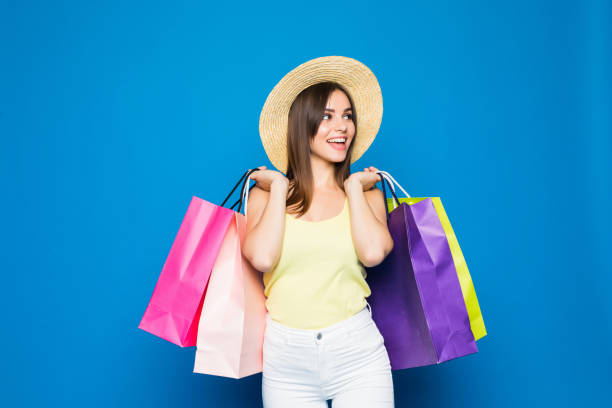 Fashion portrait young smiling woman wearing a shopping bags, straw hat over colorful blue background stock photo