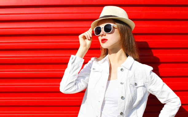 Fashion portrait young woman wearing a sunglasses and hat over red colorful background – Foto