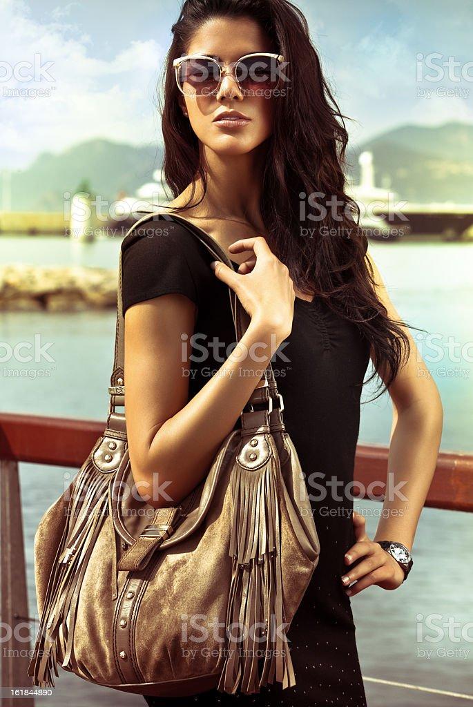 Fashion potrait of beautiful woman with bag on seacoast royalty-free stock photo