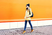 Fashion pretty blonde woman walking in city over colorful orange background