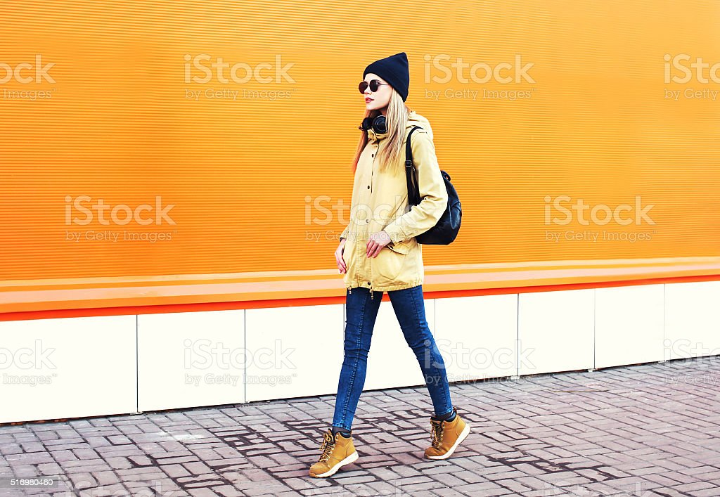 Fashion pretty blonde woman walking over colorful orange background stock photo