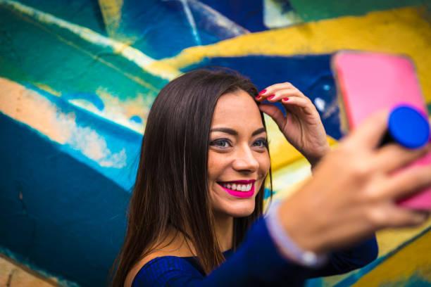 mode ziemlich sorglos frau selfie fotografieren im farbenfrohen abstrakten hintergrund - spaß sprüche stock-fotos und bilder