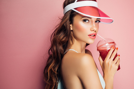 Fashion pretty cool girl drinks from cup over pink background