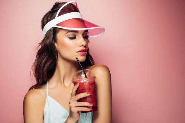 ziemlich coole mädchenmode trinkt aus der tasse über rosa hintergrund - sommer teenagermode stock-fotos und bilder