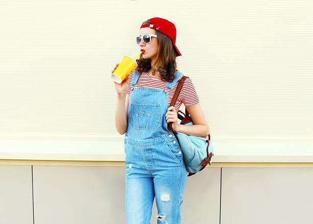 mode ziemlich cooles mädchen getränke von cup auf weißer hintergrund - jeans overall stock-fotos und bilder
