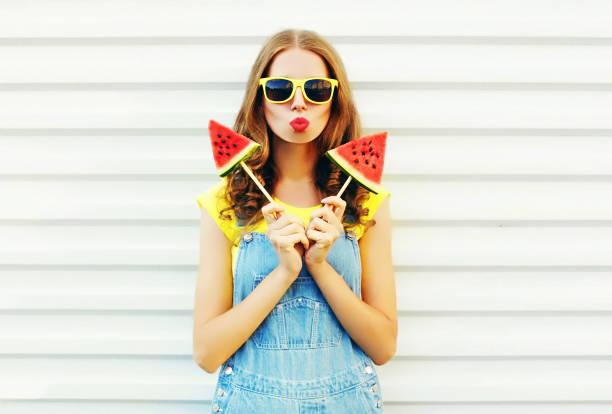 ziemlich coole mädchenmode mit ein zwei stück wassermelone eis weht ihre lippen über einen weißen hintergrund - jeans overall stock-fotos und bilder