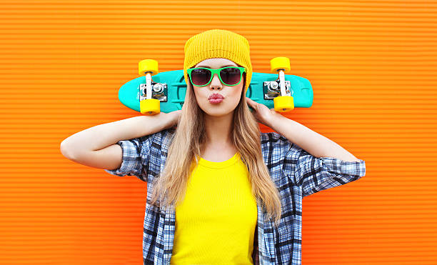 Fashion pretty cool girl with skateboard over colorful orange background stock photo