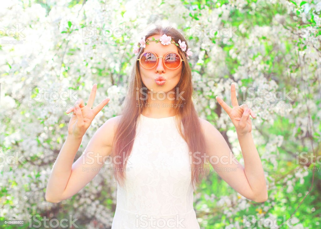 Fashion pretty cool hippie girl having fun over flowering garden background stock photo