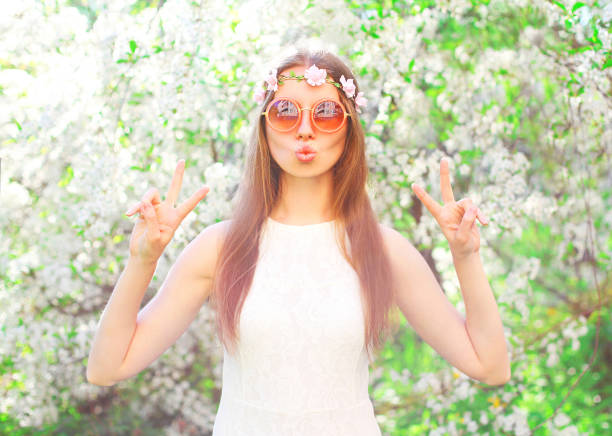 fashion pretty cool hippie girl having fun over flowering garden background - hippie fashion stock photos and pictures