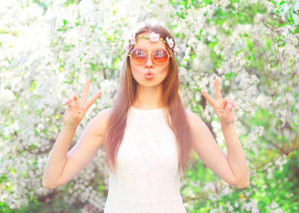 Fashion pretty cool hippie girl having fun over flowering garden background stock photo