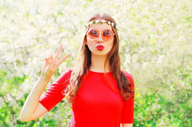 ziemlich coole hippie-mädchen fotomodell spaß über blühende garten hintergrund - hippie stirnbänder stock-fotos und bilder