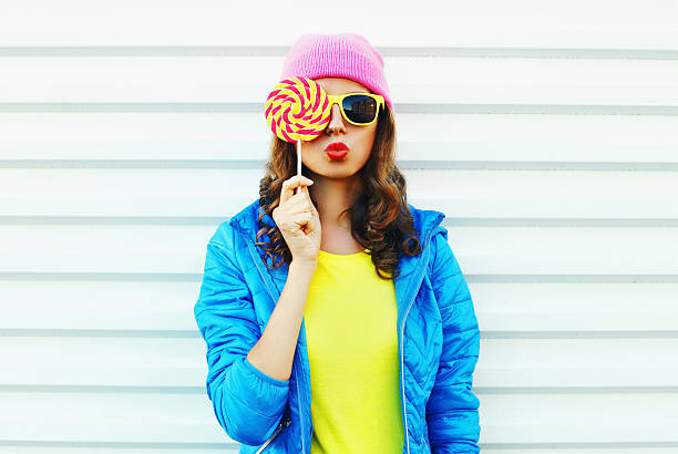 fashion pretty cool woman with lollipop in colorful clothes stock photo