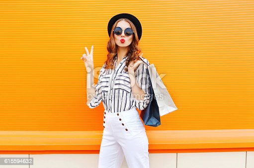 istock Fashion pretty cool young girl with shopping bags wearing hat 615594632