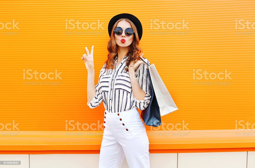 Fashion pretty cool young girl with shopping bags wearing hat stock photo