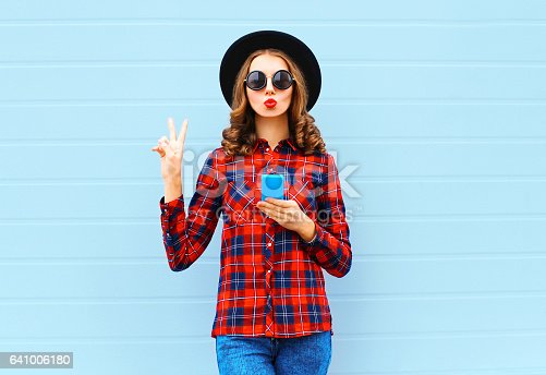 istock Fashion pretty cool young woman with smartphone blowing red lips making air kiss outdoors in city, wearing black hat and red checkered shirt 641006180