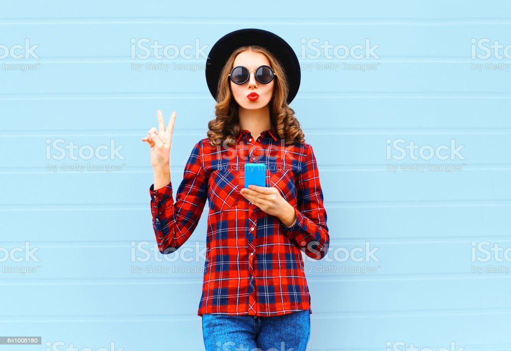 Fashion pretty cool young woman with smartphone blowing red lips making air kiss outdoors in city, wearing black hat and red checkered shirt stock photo