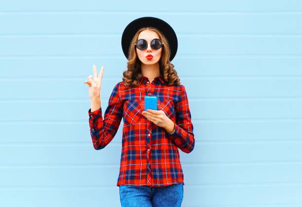ziemlich coole mode junge frau mit rote lippen, so dass luft kuss im freien in stadt, mit schwarzem hut und rot kariertes hemd weht smartphone - rotes oberteil stock-fotos und bilder