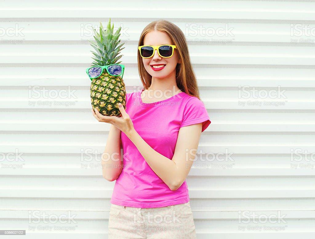 白い背景の上のパイナップルとサングラスのファッションかわいい女の子